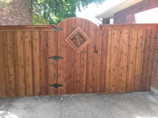 Privacy fence with custom wood gate with metal finishes.