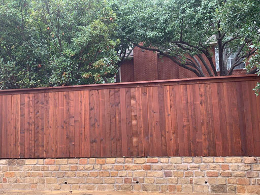 Tall privacy fence with house behind
