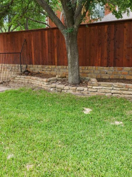 stained privacy fence on stone wall