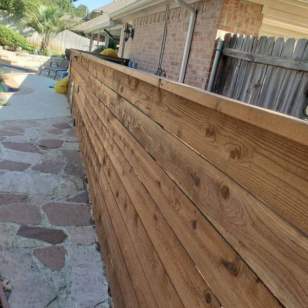 backyard horizontal wood fence next to a house and swimming pool