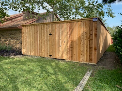 Wooden board on board residential fencing with a gate