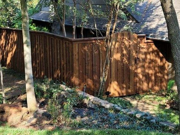 Wooden residential fencing with a gate going into a backyard